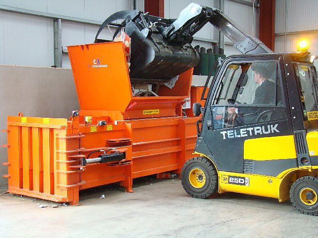 Horizontal Baler being loaded by fork lift
